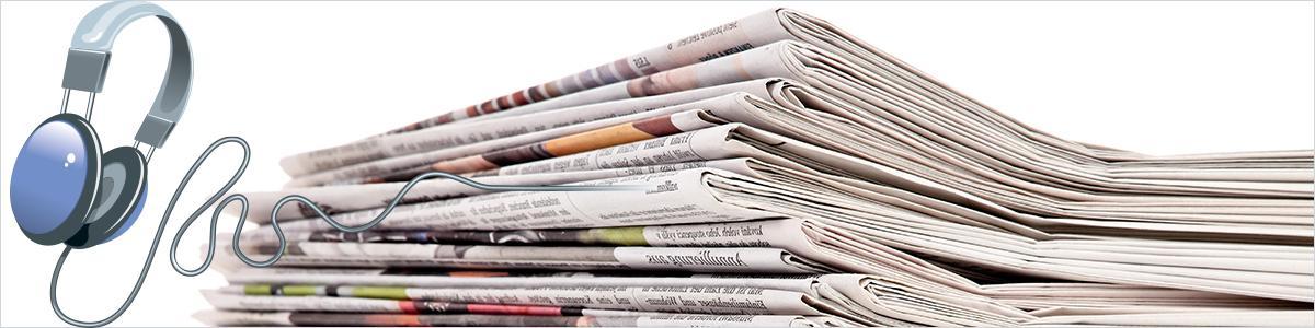 En stak forskellige aviser samt et sæt høretelefoner