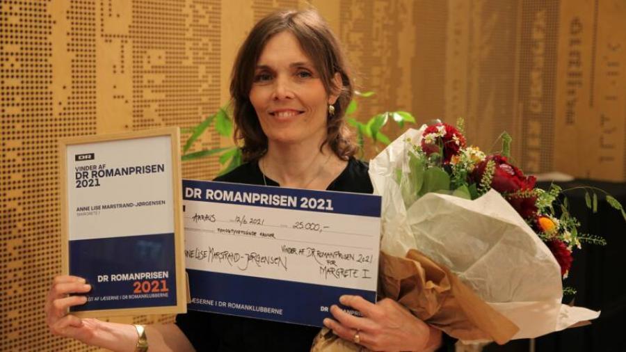 Foto af Anne Lise Marstrand-Jørgensen med DR-Romanprisen 2021 i hånden