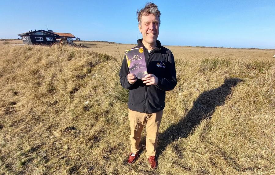 """Thomas holder romanen """"Kaptajnen og Ann Barbara"""" i hænderne i et hedelandskab"""